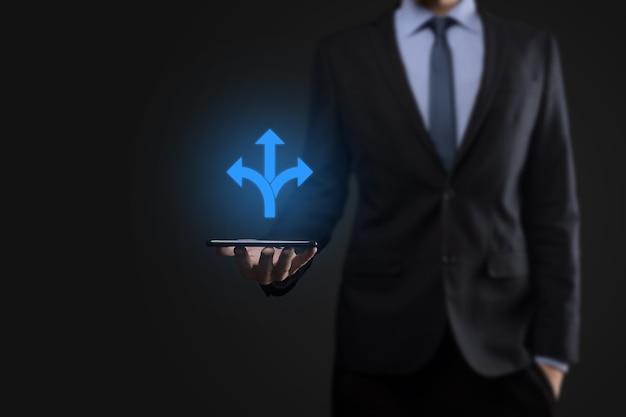 Biznesmen w garniturze trzyma znak wskazujący trzy kierunki. wątpliwości, koniecznością wyboru między trzema różnymi możliwościami wskazanymi przez strzałki skierowane w przeciwnym kierunku koncepcji. trzy sposoby wyboru