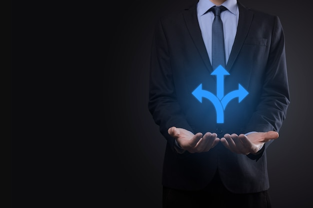 Biznesmen w garniturze trzyma znak wskazujący trzy kierunki. wątpliwości, koniecznością wyboru pomiędzy trzema różnymi możliwościami wskazanymi przez strzałki skierowane w przeciwnym kierunku koncepcji. trzy sposoby wyboru