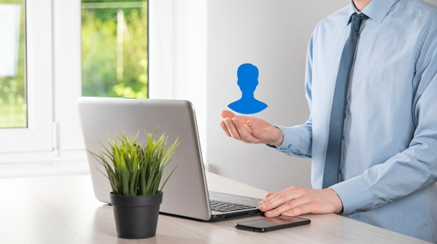 Biznesmen w garniturze trzymając ikonę dłoni użytkownika. ikony internetu na pierwszym planie. globalna koncepcja mediów sieciowych, kontakt na wirtualnych ekranach, kopia przestrzeń