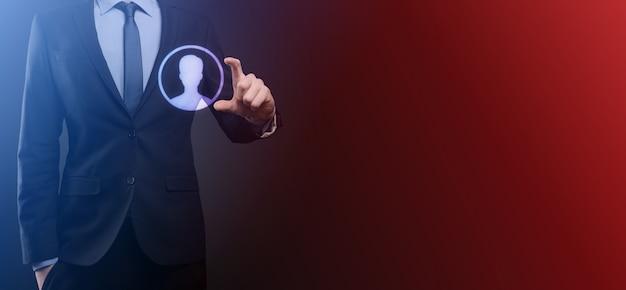 Biznesmen w garniturze trzymając ikonę dłoni użytkownika. ikony internetu na pierwszym planie. globalna koncepcja mediów sieciowych, kontakt na wirtualnych ekranach, kopia przestrzeń.
