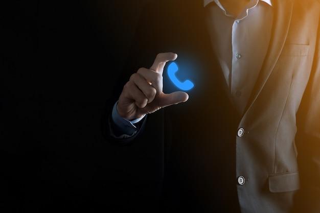 Biznesmen w garniturze, trzymając ikonę telefonu