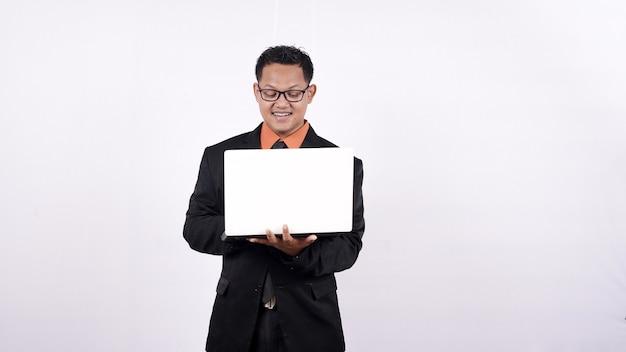 Biznesmen w garniturze, trzymając laptopa i patrząc w kamerę na białym tle