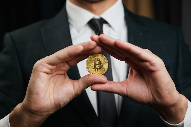 Biznesmen w garniturze, trzymając złote bitcoiny na czarnym tle