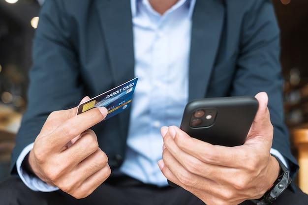 Biznesmen w garniturze trzymający kartę kredytową i używający smartfona z ekranem dotykowym do zakupów online podczas składania zamówień w kawiarni lub biurze. koncepcja biznesowa, technologia, e-commerce i płatności online