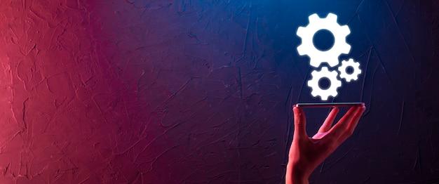 Biznesmen w garniturze trzymający metalowe koła zębate i mechanizm koła zębatego reprezentujący koncepcję współpracy zespołowej interakcji, trzymający rękę grupę kół zębatych wirtualnych kół zębatych