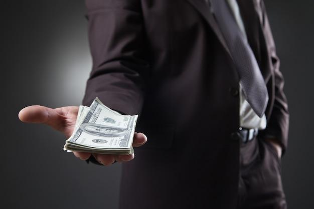 Biznesmen w garniturze trzymający pieniądze na ciemności