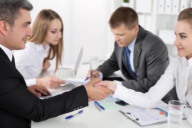 Biznesmen w garniturze uścisk dłoni kobiety z kolegami. partnerzy zawarli umowę i zapieczętowali ją klamrami. formalny gest powitania
