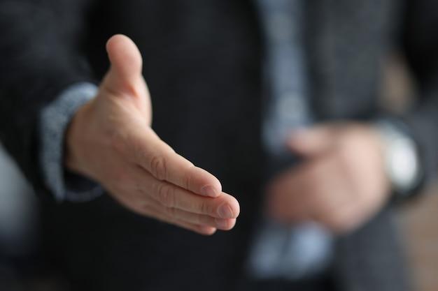 Biznesmen w garniturze wyciągając rękę do uścisku dłoni z partnerem z bliska