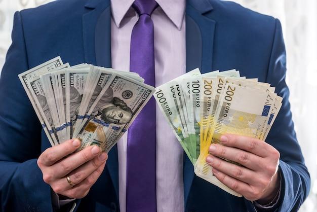 Biznesmen w garniturze z fanem euro i dolara