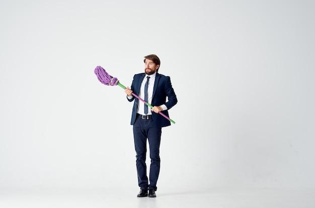 Biznesmen w garniturze z mopem w dłoniach usługi sprzątania