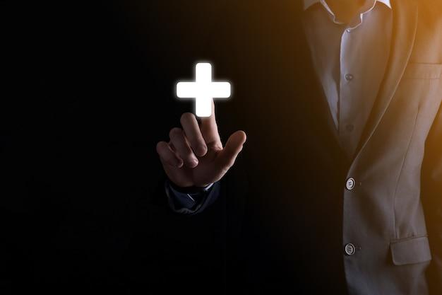 Biznesmen w garniturze z wyciągniętym palcem na dłoni klika ikonę plusa.