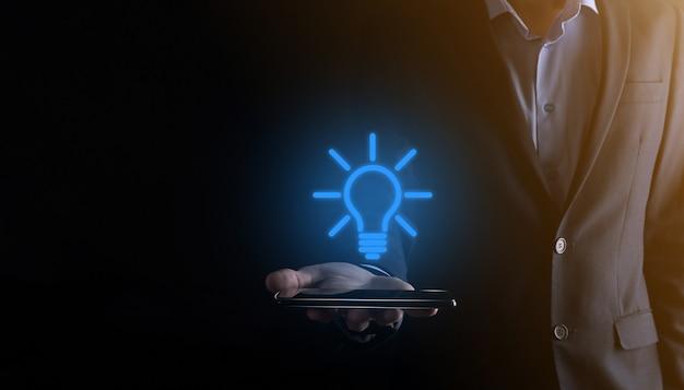 Biznesmen w garniturze z żarówką w rękach. trzyma w dłoni świecącą ikonę pomysłu na smartfonie.