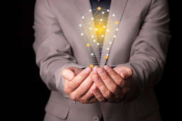 Biznesmen w garniturze z żarówką w rękach. trzyma w dłoni świecącą ikonę pomysłu. z miejscem na tekst. zdjęcie wysokiej jakości