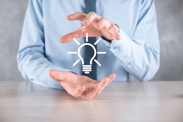 Biznesmen w garniturze z żarówką w rękach. w dłoni trzyma świecącą ikonę pomysłu. z miejscem na tekst.