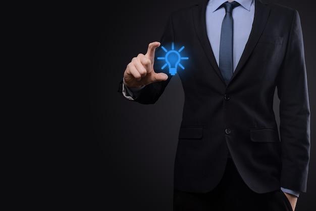 Biznesmen w garniturze z żarówką w rękach. w dłoni trzyma świecącą ikonę pomysłu