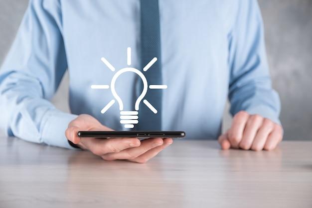 Biznesmen w garniturze z żarówką w ręku. trzyma w dłoni świecącą ikonę pomysłu. z miejscem na tekst.