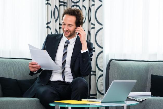 Biznesmen w hotelu biznesowym rozmawia przez telefon