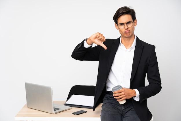 Biznesmen w jego biurze nad biel ścianą pokazuje kciuka puszka znaka