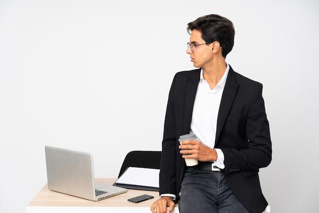 Biznesmen w jego biurze nad odosobnioną ścienną biel ściany przyglądającą stroną