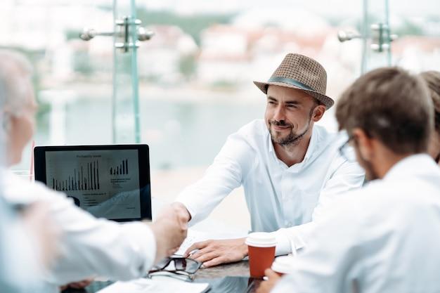 Biznesmen w kapeluszu uścisk dłoni ze swoim partnerem biznesowym