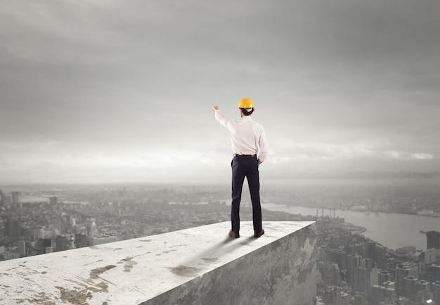 Biznesmen w kasku wskazuje właściwy kierunek na dachu nad miastem