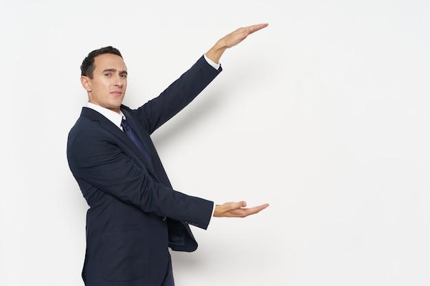 Biznesmen w klasycznym garniturze rozkłada ręce w górę iw dół menedżer finansów