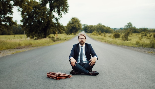 Biznesmen w klasycznym garniturze siedzi na środku drogi i medytuje z zamkniętymi oczami