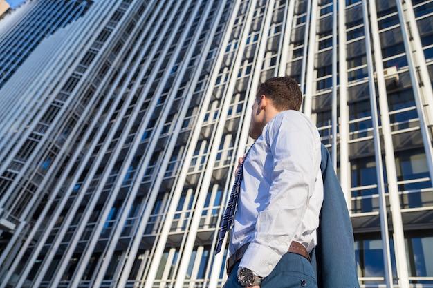 Biznesmen w klasycznym garniturze, trzymając kurtkę na tle nowoczesnego biurowca wieżowiec.