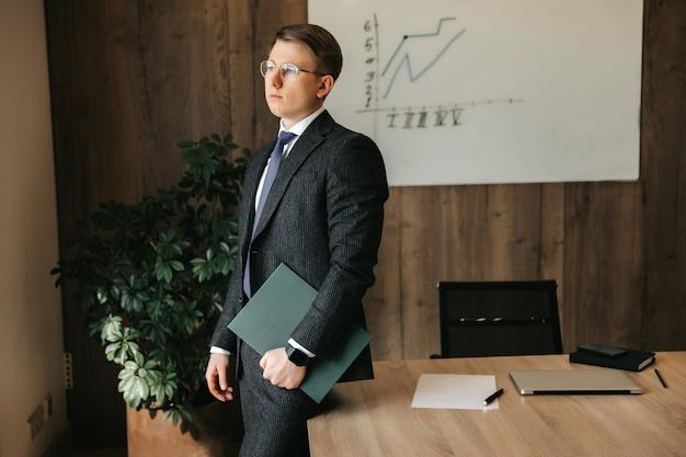 Biznesmen w klasycznym garniturze w biurze trzyma w rękach teczkę z dokumentami.
