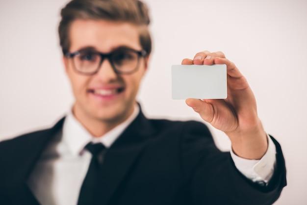 Biznesmen w kostiumu i eyeglasses trzyma pustą wizytówkę.