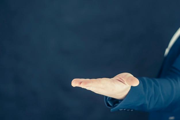 Biznesmen w koszuli i niebieskiej kurtce pokazuje gesty rękami.