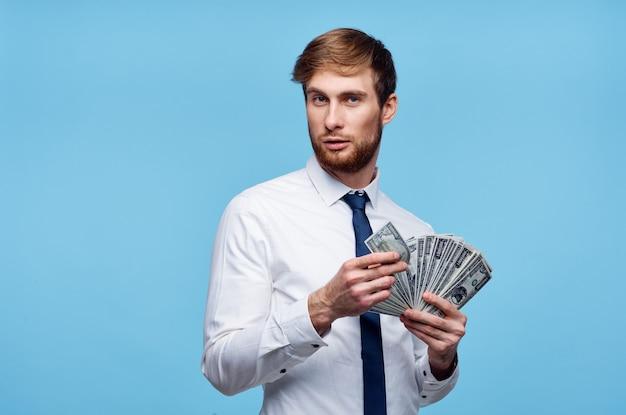 Biznesmen w koszuli trzyma banknoty dolarowe