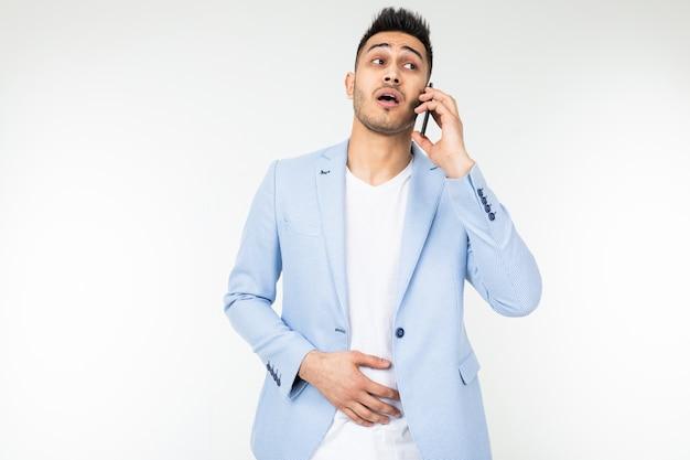 Biznesmen w kurtce omawia ważne sprawy przez telefon na białym tle.