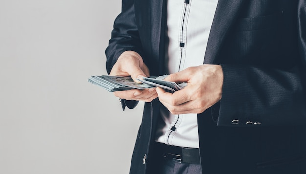 Biznesmen w luksusowym czarnym kostiumu trzyma dolary w jego rękach. mężczyzna liczy swoje pieniądze