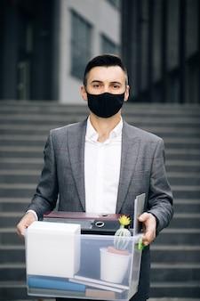 Biznesmen w masce medycznej niesie pudełko z rzeczami osobistymi wychodząc z biura