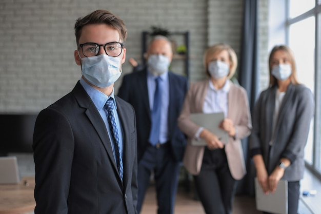 Biznesmen w masce medycznej z kolegami w tle w biurze.