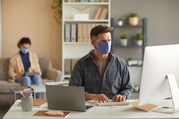Biznesmen w masce ochronnej pracy na komputerze przy stole z kolegą w ścianie w biurze