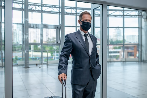 Biznesmen w masce ochronnej z walizką