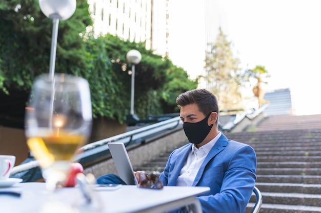 Biznesmen w masce siedzi w kawiarni. młody człowiek za pomocą laptopa na zewnątrz. pomysł na biznes.