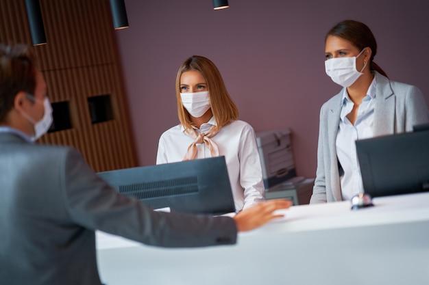 Biznesmen w masce w recepcji hotelu melduje się