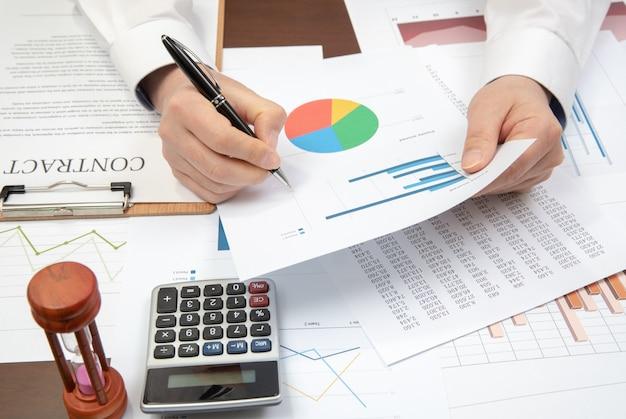 Biznesmen w miejscu pracy. kontrakty, wykresy i wykresy na biurku.