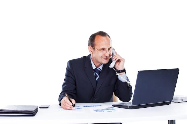 Biznesmen w miejscu pracy w biurze laptopa rozmawia przez telefon
