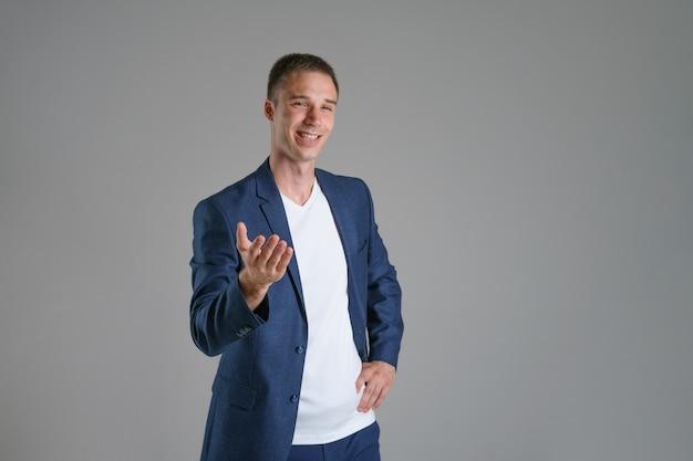 Biznesmen w niebieskiej kurtce na szarej powierzchni gestykuluje na bok, kopia przestrzeń