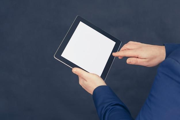 Biznesmen w niebieskiej kurtce trzyma makietę tabletu z białym ekranem
