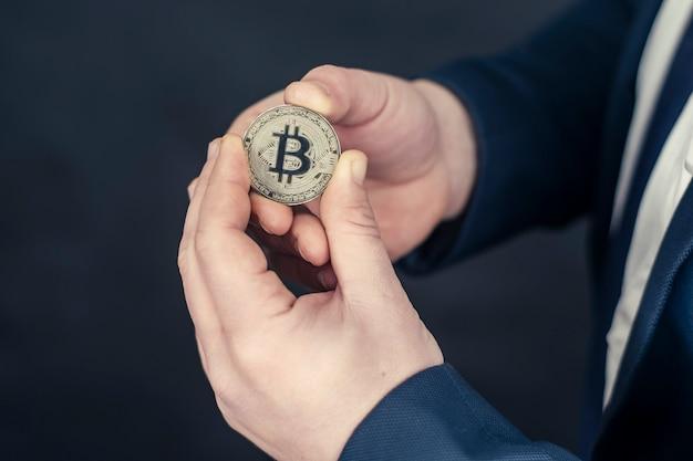 Biznesmen w niebieskiej kurtce, trzymając w rękach bitcoin. koncepcja wirtualnej waluty i blockchain.
