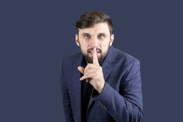 Biznesmen w niebieskim garniturze przykłada palec do ust, co oznacza ciszę
