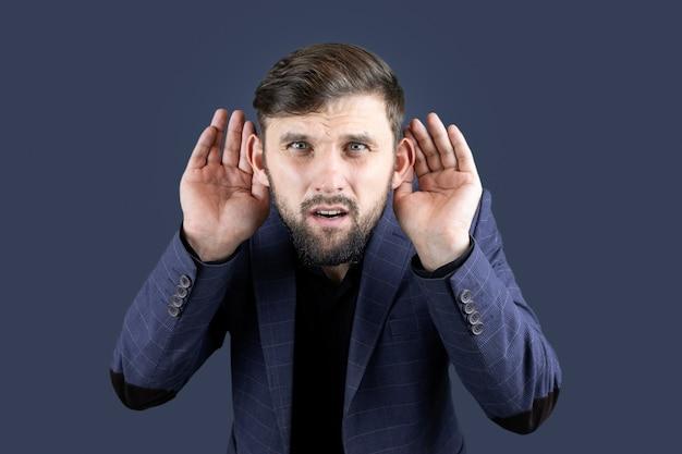 Biznesmen w niebieskim garniturze przykłada rękę do ucha, próbując coś usłyszeć.