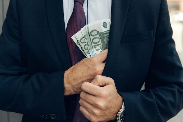 Biznesmen w niebieskim garniturze wkłada pieniądze do kieszeni. pomysł na biznes.