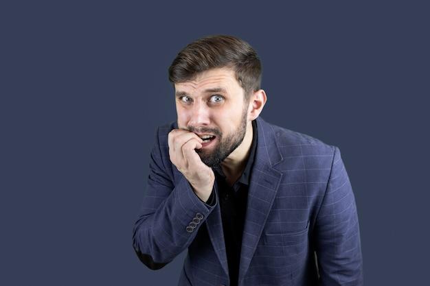 Biznesmen w niebieskim garniturze ze strachu obgryza paznokcie