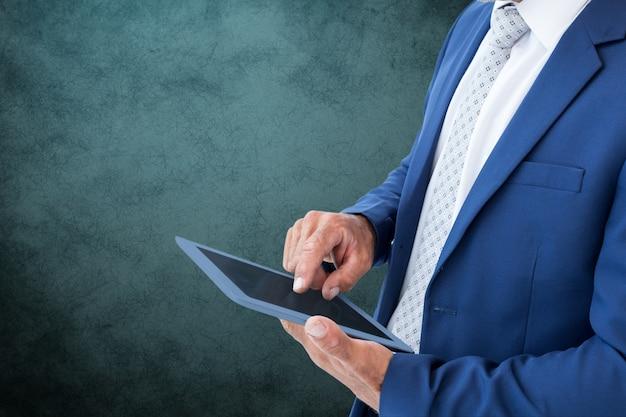 Biznesmen w niebieskim kolorze pracy ze swoim tabletem